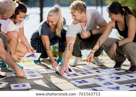 Business People Smiling While Solving Crossword On Patio