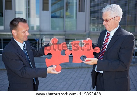Business people solving a problem symbolized with two red jigsaw puzzle pieces - stock photo