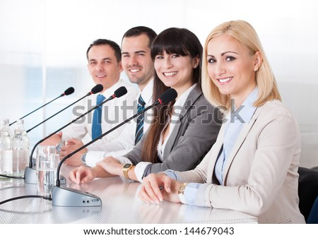 Business People Speaking In Microphone In Office