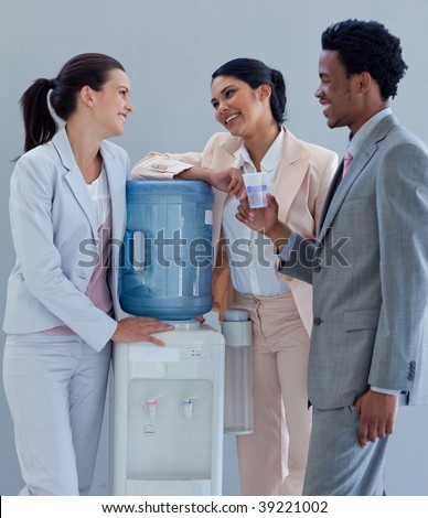 Business people speaking next to a water cooler in office - stock photo