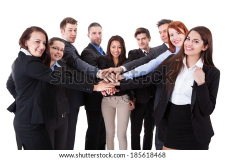 Business people stacking hands over white background
