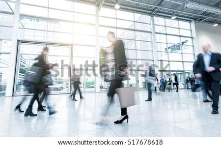 business people standing and walking on a trade fair floor