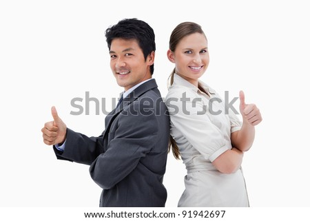 Business people standing back to back with the thumb up against a white background