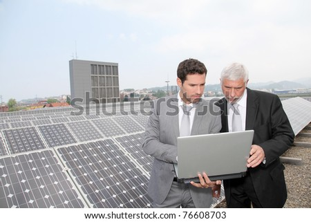 Business people standing by solar panels - stock photo