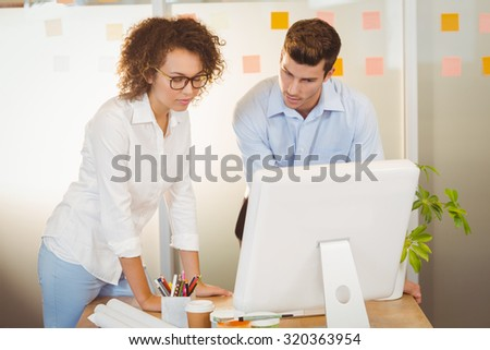 Business people standing by table using computer in office