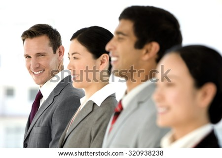 Business people standing in a row. Selective focus on the man looking at camera