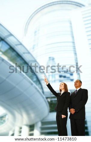 business people standing in front of modern building. the woman pointing up to somewhere. concept for success or business plan - stock photo