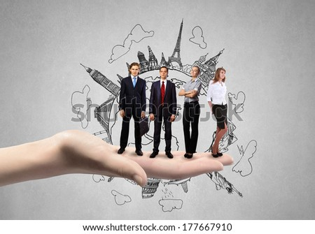 Business people standing on palm with construction sketch at background - stock photo
