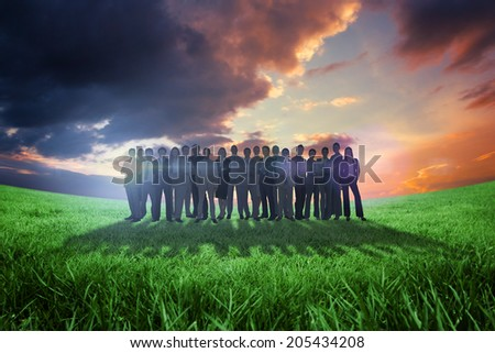 Business people standing up against green field under orange sky - stock photo