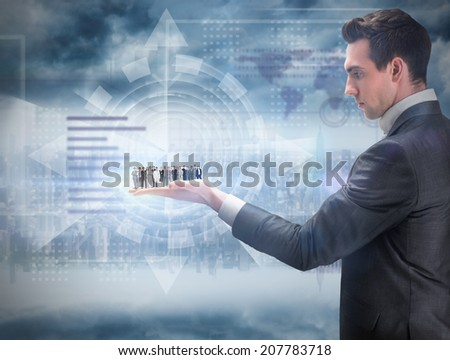 Business people standing up held by giant businessman against room with large window looking on city - stock photo