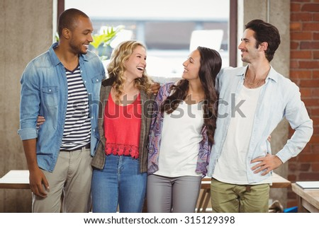 Business people standing with arms around and laughing in creative office - stock photo