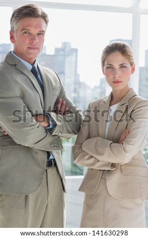 Business people standing with their arms crossed in a bright office - stock photo