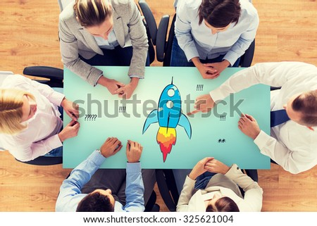 business, people, startup, development and team work concept - close up of creative team sitting at table and pointing finger to rocket icon in office - stock photo