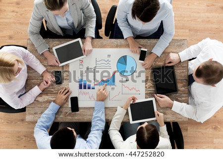 business, people, statistics and team work concept - close up of creative team with charts on paper, smartphones and tablet pc computers sitting at table in office