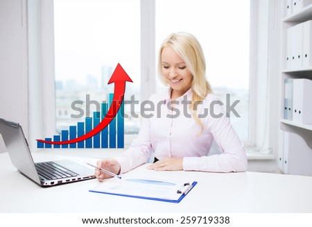 business, people, statistics and technology concept - smiling businesswoman with laptop computer, papers and growing chart sitting in office - stock photo