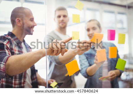 Business people sticking adhesive notes on glass window in creative office - stock photo
