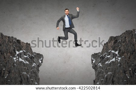 business, people, success, achievement and education concept - happy smiling businessman jumping between two rocks