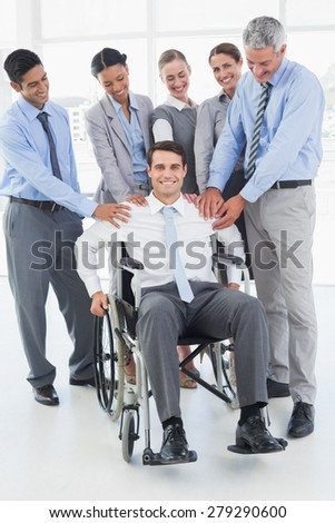 Business people supporting their colleague in wheelchair in office - stock photo
