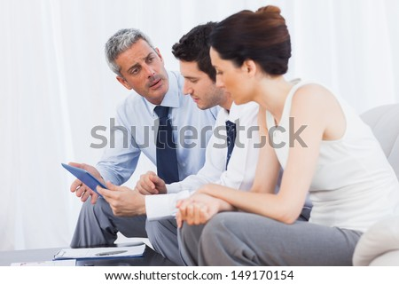 Business people talking about files on sofa at office - stock photo
