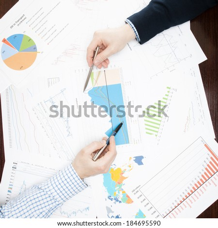 Business people talking about financial data - view from the top - 1 to 1 ratio - stock photo