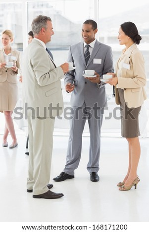 Business people talking and drinking coffee at a conference in the office - stock photo