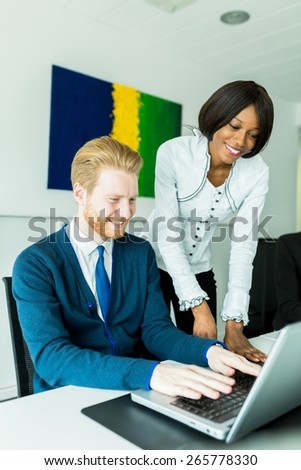 Business people talking and smiling in an office in front of a notebook - stock photo