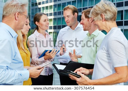 Business people talking and working together with a tablet PC - stock photo