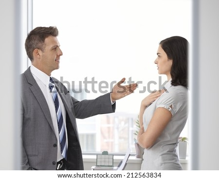 Business people talking front of window at office. Standing, looking at each other. Suit, explanation, gesturing - stock photo