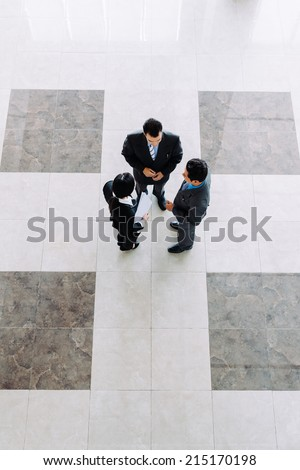 Business people talking in office lobby, view from the top - stock photo