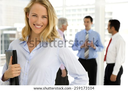 Business people talking in the background and pretty businesswoman looking at camera on foreground - stock photo