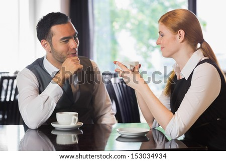 Business people talking over coffee in a cafe - stock photo