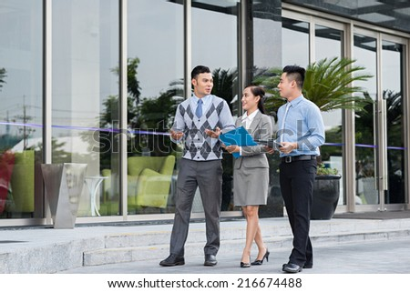 Business people talking while walking along the street - stock photo