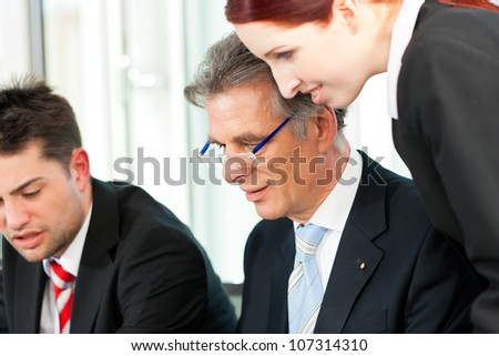 Business people - team meeting in an office, the boss with his employees - stock photo
