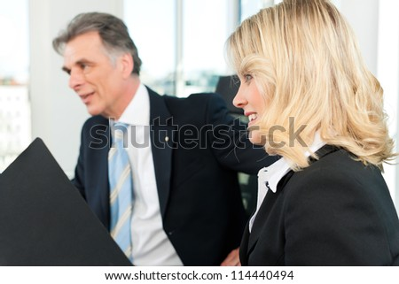 Business people - team meeting in an office, the boss with his secretary - stock photo