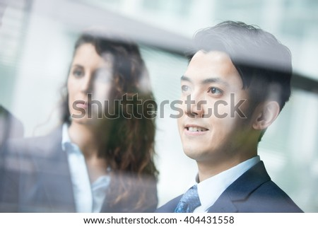 Business people team meeting in front of the office window, asian and caucasian - stock photo