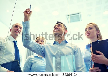 business, people, teamwork and planning concept - smiling business team writing something no notice board with marker in office - stock photo