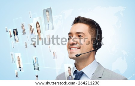 business, people, technology and customer service concept - smiling businessman in headset looking to virtual contacts icons projection over blue background - stock photo