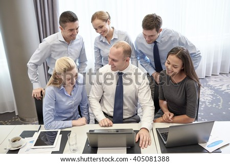 business, people, technology and teamwork concept - smiling business team with laptop computers working in office