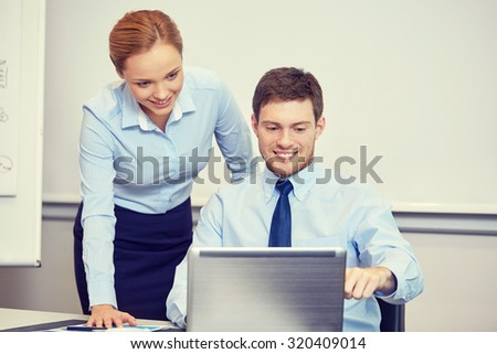 business, people, technology and teamwork concept - smiling businessman and businesswoman with laptop computer meeting and talking in office - stock photo