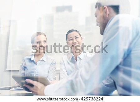 business, people, technology and teamwork concept - smiling businessman and businesswomen with tablet pc computer meeting in office - stock photo
