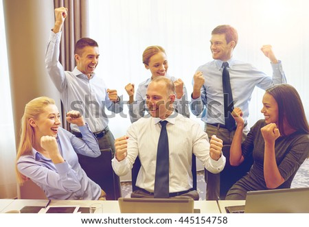 business, people, technology, gesture and teamwork concept - smiling business team raising hands and celebrating victory in office - stock photo