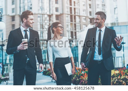 Business people. Three cheerful young business people talking to each other while walking outdoors