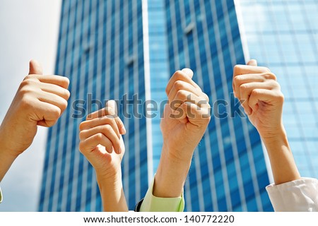 Business people thump up together showing sign ok over office building - stock photo