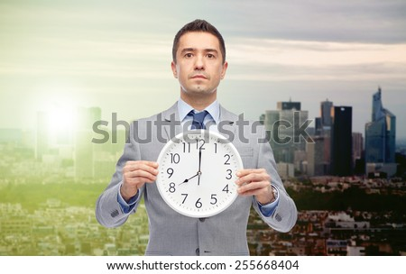 business, people, time difference and work concept - businessman holding clock showing 8 o'clock over sunrise and sunset in city background - stock photo