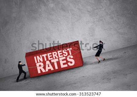 Business people trying to get a block with interest rates word on it