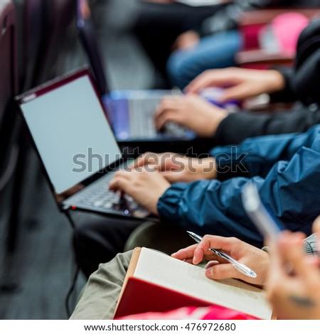 Business people typing on laptop keyboard at conference.