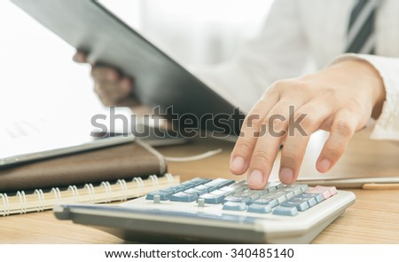 Business people using a calculator to calculate the numbers - stock photo