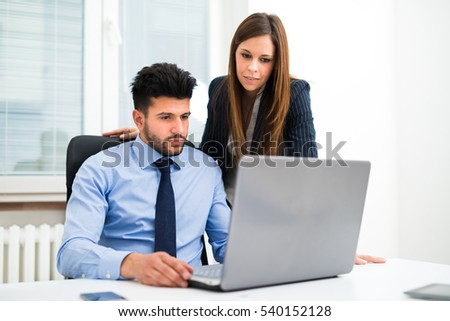 Business people using a laptop computer in their office. Shallow depth of field, focus on the woman