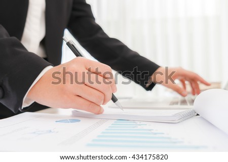 Business people using a pencil noting over laptop