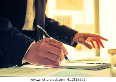 Business people using a pencil noting over laptop ( Filtered image processed vintage effect. )